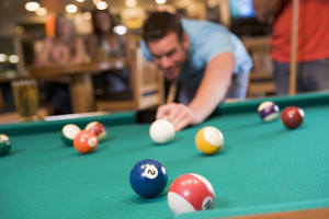Young man playing pool in a bar (focus on pool table)