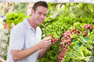 Young man shopping for fresh produce in supermarket