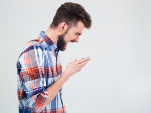 Young man shouting on smartphone
