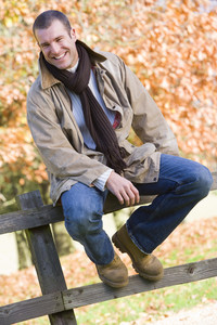 Young man sitting on fence with autumn leaves behind