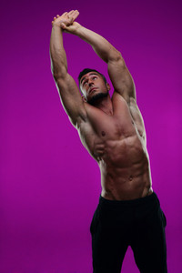 Young man stretching hands on pink background