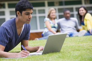 Young man using laptop on campus lawn, with other students relaxing in background