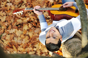 Young man with guitar in park