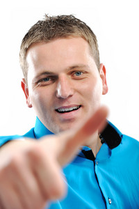 Young man with thumbs up pointing towards camera