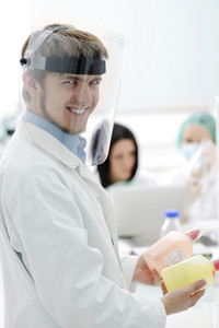 Young medical worker with glass mask working with his team in lab