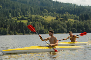 Young men kayaking summertime vacation on river paddling