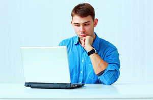 Young pensive businessman in blue shirt sitting at the table with laptop in office