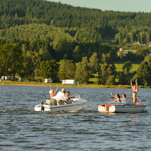 Young people having fun on motorboats on lake summertime