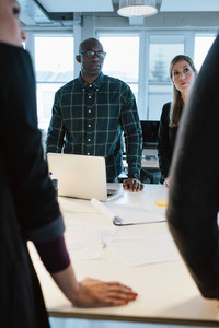 Young people standing at a table discussing work. African man with caucasian woman in office during meeting.