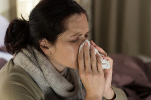 Young sick woman sneezing in tissue sweating from flu fever