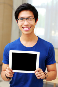 Young smiling asian man showing blank tablet computer screen at home