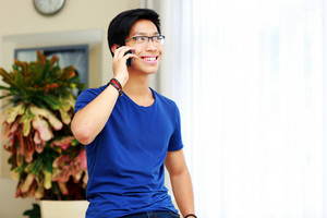 Young smiling Asian man talking on the phone