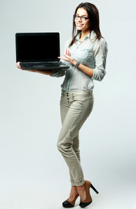 Young smiling businesswoman showing laptop on gray background