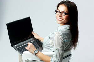 Young smiling businesswoman using laptop and looking at camera on gray background