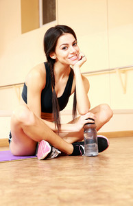 Young smiling fit woman resting on the floor with bottle of water at gym
