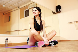 Young smiling fit woman sitting on yoga mat and looking away at gym