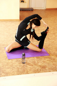 Young smiling fit woman stretching on yoga mat at gym