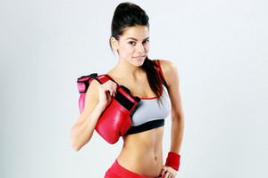 Young smiling fitness woman standing with boxing gloves on gray background