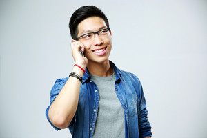 Young smiling man talking on the phone over gray background