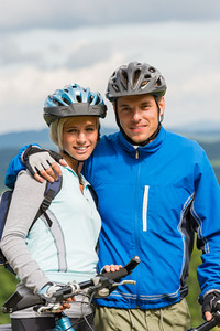 Young smiling sporty couple with bicycles in helmet