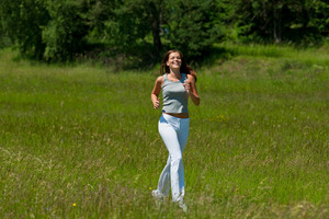 Young smiling woman jogging in the nature,shallow DOF