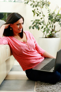 Young smiling woman sitting on the floor and using laptop at home