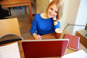 Young smiling woman using laptop in office