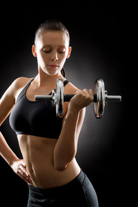 Young sport woman holding adjustable dumbbell on black background