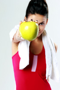 Young sport woman holding apple on gray background