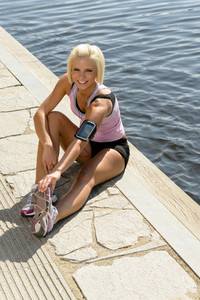 Young sport woman stretch legs sitting by water pier summer