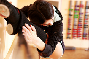 Young sport woman stretching at gym