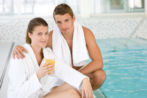 Young sportive couple relax at swimming pool in luxury hotel