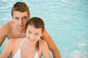 Young sportive couple relax in pool in luxury spa