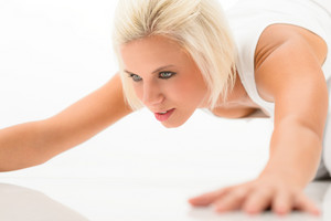 Young sportive woman doing push-ups on white background fitness exercise