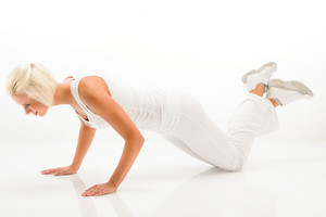 Young sportive woman doing pushups on white background