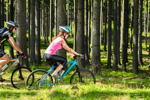 Young sporty biker couple in woods sunny day in countryside