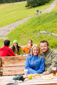Young sporty tourists drinking refreshments and resting on wooden bench
