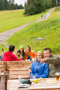 Young sporty tourists resting on wooden bench nature pointing direction