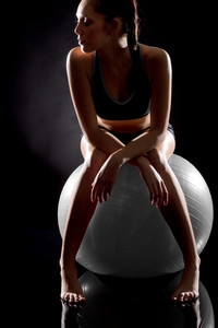 Young sporty woman relaxing on fitness ball on black background