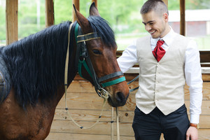 Young stylish man taking riding a horse on countryside