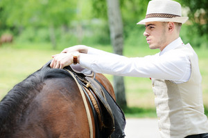 Young stylish man with tie and hat riding a horse on countryside