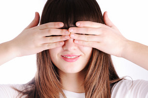 Young teen woman covering her eyes isolated on white background