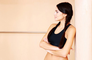 Young thoughtful fit woman looking away at gym