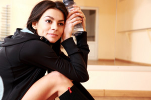 Young thoughtful fit woman resting and holding botter of water at gym