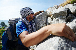 Young white man climbing a steep wall in mountain, rock climbing and hiking extreme sport