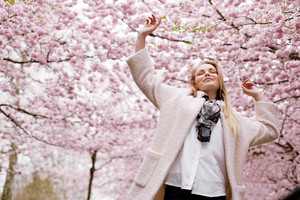 Young woman arms raised enjoying the fresh air in spring park. Carefree young female at spring blossom garden - Outdoors