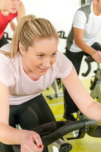 Young woman at bike spinning class enjoy cardio training