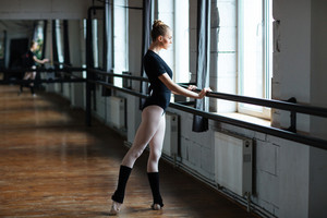 Young woman doing stretching exercises in ballet class