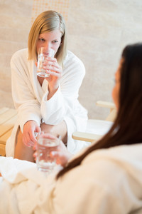 Young woman drink water with friend at beauty spa