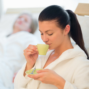 Young woman drinking coffee at spa with friend in background